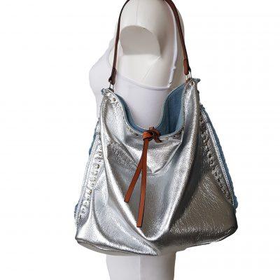 tas zilver spijkerstof Deze super leuke glanstas zilver met spijkerstof is gemaakt van een soepel vallende glanzende stof afgewerkt met gekleurde metalen spijkes in de zijkanten van de tas. Dit leuke model valt nonchalant om de schouders, en zakt met dragen een beetje in Het leuke van dit model is dat je deze om binnenste buiten kunt keren waardoor je beide kanten van de tas kunt dragen, de spijkerstof of de zilverenglans stof als look. De tas wordt geleverd met twee hengsels in verschillende lengtes om te dragen als handtas of schoudertas. Aan beide zijkanten van de ritsen zit een leuke versiering in de vorm van een leren knoopje. Deze tas is een echte eyecatcher en geeft een heerlijk zomers gevoel van zon strand en bling bling size 30 cm hoog 40 cm breed